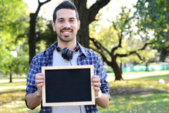 Young man with black headphones holding chalkboard . Stock Photography