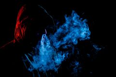 A young man in a black hood smokes. A vape and exhales a colored  red and blue smoke on a black isolated background Stock Images