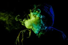 A young man in a black hood smokes. A vape and exhales a colored  green and blue smoke on a black isolated background Stock Photos