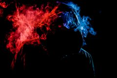 A young man in a black hood smokes. A vape and exhales a colored  red and blue smoke on a black isolated background Royalty Free Stock Photography