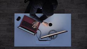 Young man in black hoodie drinking coffee and typing on laptop during night, sitting behind white desk, top shot.  stock footage