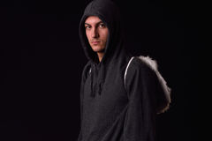 Young man with black hoodie and white feathered wings behind the. Back on a dark background. Conceptual photo, good and bad Royalty Free Stock Photo
