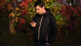 Young man in black jacket in the autumn park using his smartphone stock video