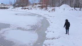 Young man in black jacket with fur hood is on snow-covered Bank of frozen river and checks the ice. Backside view young man in black jacket with fur hood is on stock video