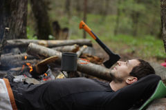 A young man in a black jacket lying around the campfire Stock Photography