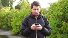 Young man in black jacket surf the internet using his smartphone outdoor. HD stock footage