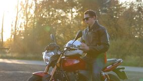 A young man in black leather jacket with white helmet goes to his motorcycle and sits on it before journey at autumn sunset. Close up shot stock video