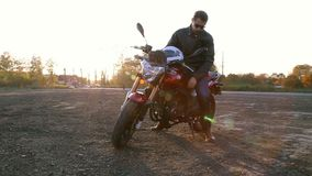 A young man in black leather jacket with white helmet goes to his motorcycle and sits on it before journey at autumn sunset. Steady cam shot stock video