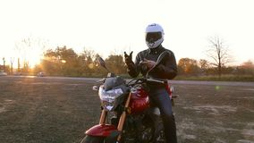 A young man in black leather jacket and white helmet sits on motorcycle puts on protective gloves before journey at autumn sunset. Steady cam shot stock video