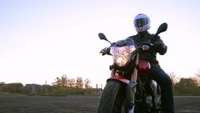 A young man in black leather jacket and white helmet sits on motorcycle turns on lights before journey at autumn sunset. Steady cam shot stock footage