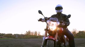 A young man in black leather jacket and white helmet sits on motorcycle turns on lights before journey at autumn sunset. Steady cam shot stock video footage