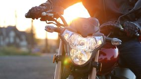 A young man in black leather jacket and white helmet sits on motorcycle turns on lights before journey at autumn sunset. Steady cam shot stock video