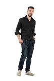 Young man in black shirt with rolled up sleeves walking. Full body length portrait isolated over white background Stock Photography