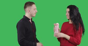 A young man in a black shirt treats an attractive brunette a hot tea from a thermo mug. stock footage