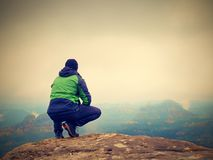 Young man in black sit on cliff& x27;s edge and looking to misty valley Stock Photo