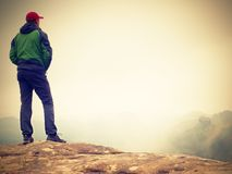 Young man in black sit on cliff& x27;s edge and looking to misty valley Royalty Free Stock Photography