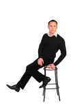Young man in black sits on stool. On white Royalty Free Stock Images