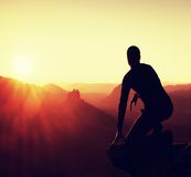 Young man in black sportswear sit on cliff edge and look into daybreak at horizon over misty valley Stock Photography