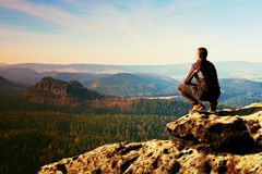 Young man in black sportswear is sitting on cliff edge and looking to misty valley bellow Royalty Free Stock Photography
