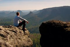 Young man in black sportswear is sitting on cliff edge and looking to misty valley bellow Royalty Free Stock Photos