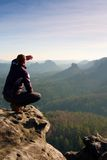 Young man in black sportswear is sitting on cliff edge and looking to misty valley bellow Royalty Free Stock Image