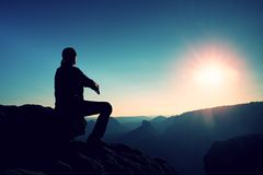 Young man in black sportswear is sitting on cliff and looking to misty valley bellow Stock Images