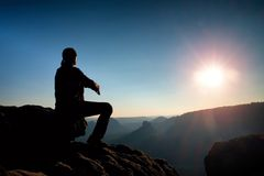Young man in black sportswear is sitting on cliff and looking to misty valley bellow Stock Photography