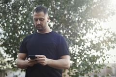 Young man typing text message on mobile phone outdoors in the park. Young man in black sportswear typing text message on mobile phone outdoors in the park Stock Photography