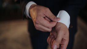 A young man in black suit adjusts his cufflinks of white shirt.