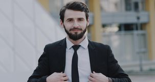 Young man in a black suit arrange his tie in front of the camera.  stock footage