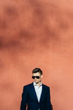 Young man in a black suit on a background of a brick wall. Man in a black jacket and dark sunglasses Royalty Free Stock Photos