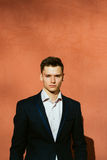 Young man in a black suit on a background of a orange wall. Man in a black jacket Royalty Free Stock Photography