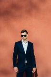 Young man in a black suit on a background of a orange wall. Man in a black jacket Royalty Free Stock Photos