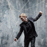 Young man in  black suit got caught on the web. Concept of manipulation and slavery Stock Images