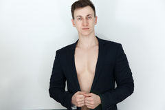 Young man in black suit with naked body. Isolated on white background Stock Photos