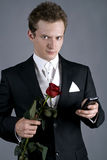 Young man in a black suit with rose and phon Royalty Free Stock Photos