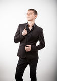 Young man in black suit standing against white background Stock Photo