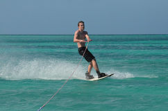 Young Man with Black Swim Shorts Wakeboarding. Wakeboarding young guy with black swim trunks in Aruba Stock Image