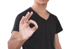 Young man in black t shirt shows sign OK. Isolated on gray backg Stock Photography
