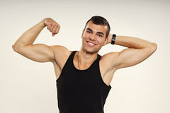 Young man in black undershirt poses. Young smiling man in black undershirt poses and shows biceps Royalty Free Stock Photo
