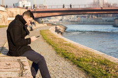 Young Man in a Black Winter Coat Sitting on The Riverbank and Lo. Oking At His Cellphone Stock Photo