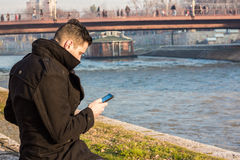 Young Man in a Black Winter Coat Sitting on The Riverbank and Lo Stock Photo