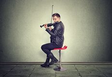 Young man on black wooden violin stock image