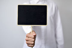 Young man with a blank black signboard. A young caucasian man wearing a white shirt shows a blank black signboard with a copy space Royalty Free Stock Images