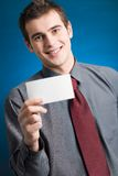 Young man with blank business card. Young businessman with blank note card on blue background Royalty Free Stock Photo