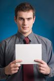 Young man with blank note card. Young businessman with blank note card on blue background Stock Images