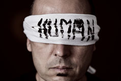Young man with a blindfold in his eyes. Closeup of a young man with a blindfold in his eyes, with the word human handwritten in it royalty free stock images