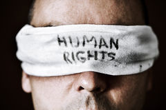 Young man with a blindfold with the text human rights. Closeup of a young man with a blindfold in his eyes with the text human rights written in it, as a symbol Stock Image