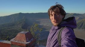 A young man blogger shoots selfie video at the viewpoint on the Bromo volcano inside the Tengger caldera on the Java