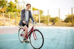 Young man with blond hair in shorts and casual shirt standing with red bicycle on basketball court in park. Thoughtful. Young man with blond hair in shorts and Stock Photo